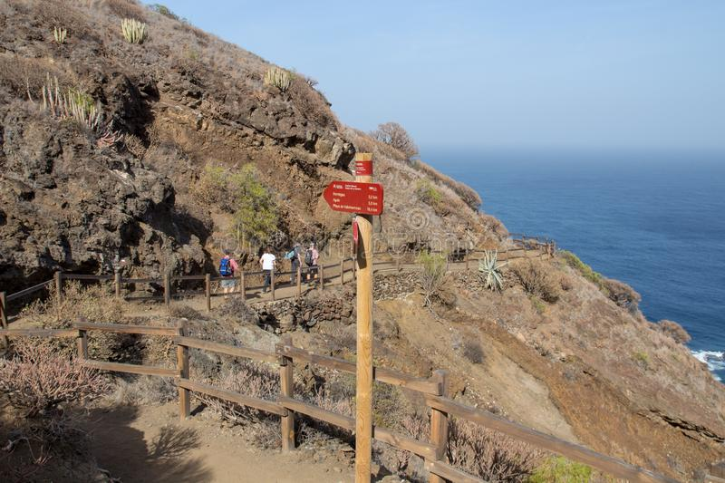 Caminhante que anda em uma fuga no norte do la Gomera Na frente deles um sinal da fuga fotos de stock