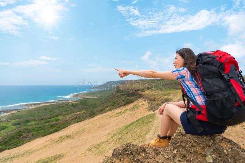 Caminhante que aponta gestos ao céu do sol e ao oceano azul imagens de stock