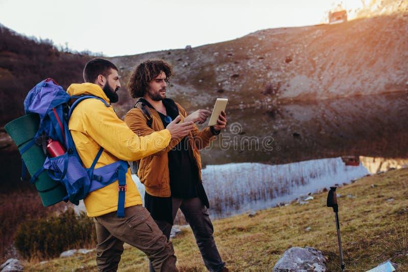 Caminhante que olha a maneira atrav?s do mapa na tabuleta digital durante a caminhada na regi?o selvagem fotos de stock