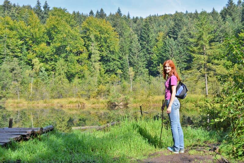 Caminhante ruivo de sorriso feliz da menina com trouxa e vara nas montanhas perto do lago inoperante nas montanhas Carpathian imagem de stock royalty free