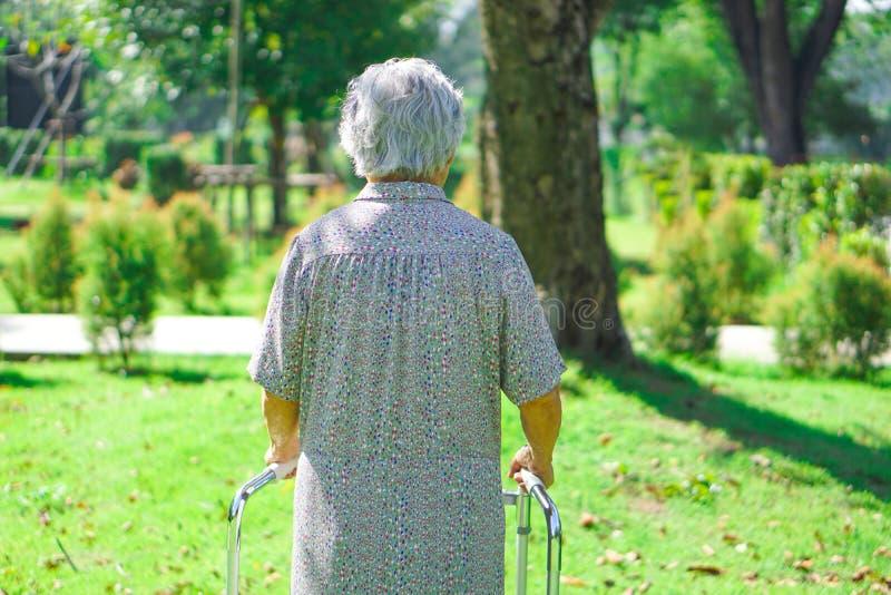 Caminhante superior ou idoso asi?tico do uso da mulher da senhora idosa com sa?de forte ao andar no parque fotografia de stock