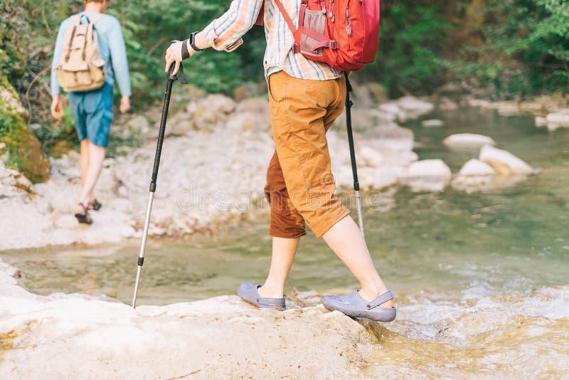 Caminhantes com as trouxas que cruzam o rio fotos de stock royalty free