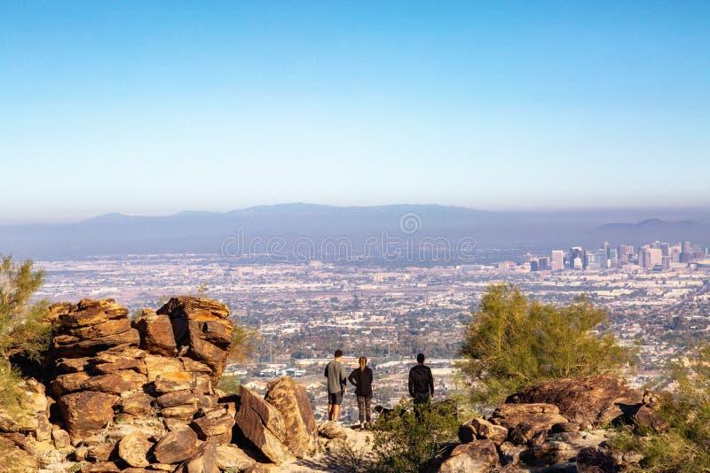 Caminhantes da montanha que negligenciam a skyline da cidade de Phoenix imagem de stock