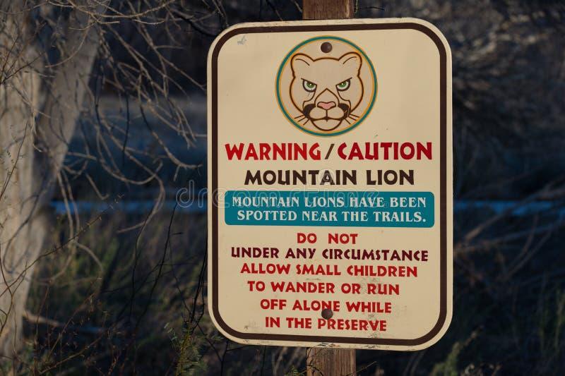 Caminhantes de advertência do sinal do parque sobre leões de montanha imagem de stock