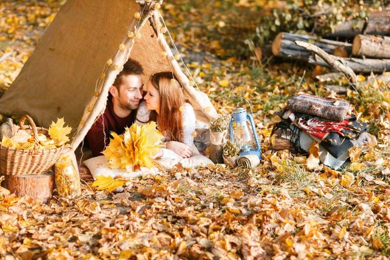 Caminhantes do homem e da mulher que acampam na natureza do outono Mochileiros novos felizes dos pares que acampam na barraca imagem de stock