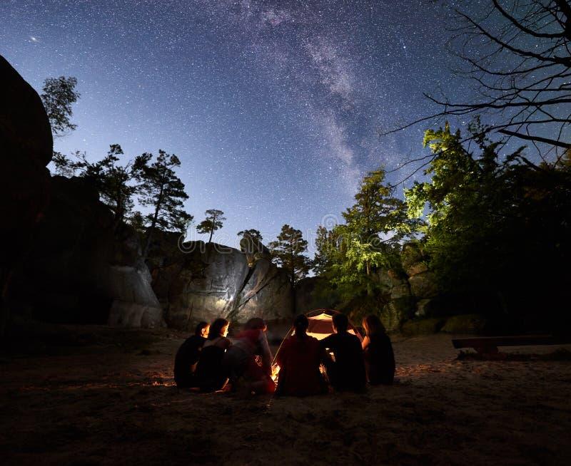 Caminhantes dos amigos que descansam ao lado do acampamento, fogueira, barraca na noite imagem de stock royalty free
