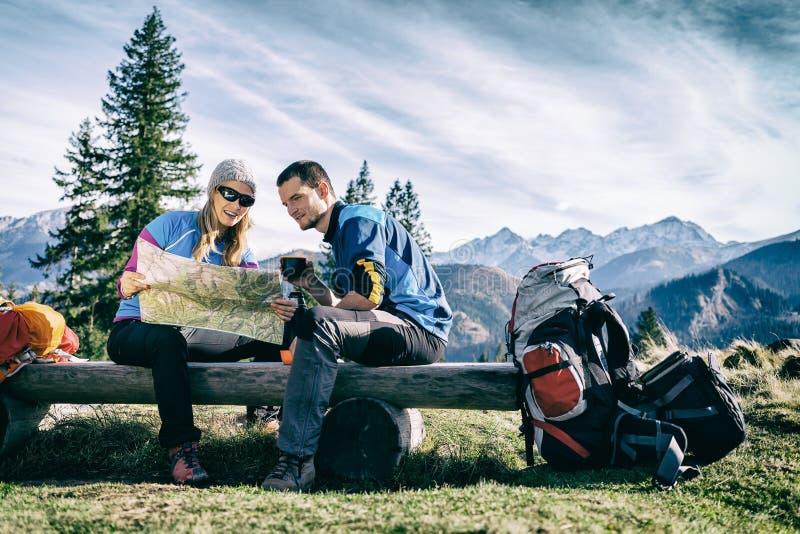 Caminhantes dos pares com o mapa nas montanhas imagens de stock royalty free