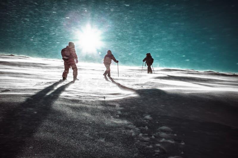 Caminhantes e queda de neve em montanhas do inverno imagens de stock