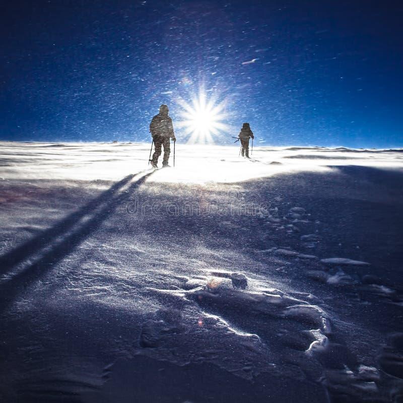 Caminhantes e queda de neve em montanhas do inverno imagem de stock royalty free