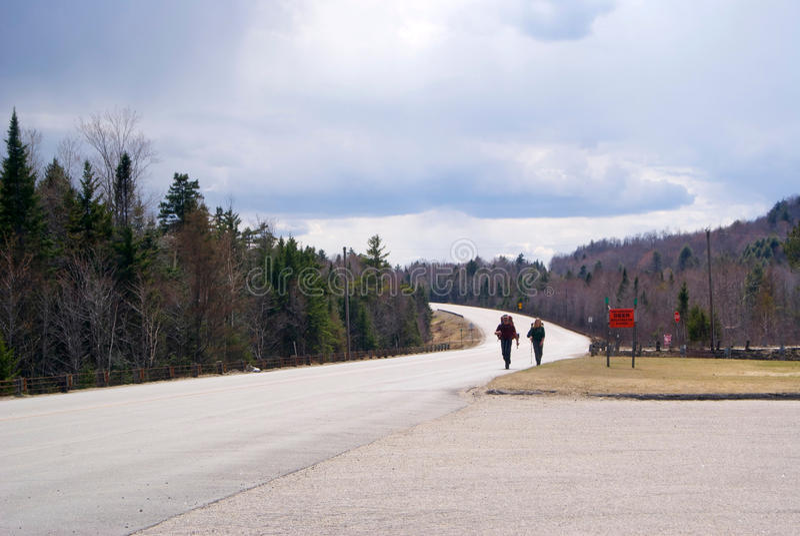 Caminhantes em uma estrada da montanha imagem de stock