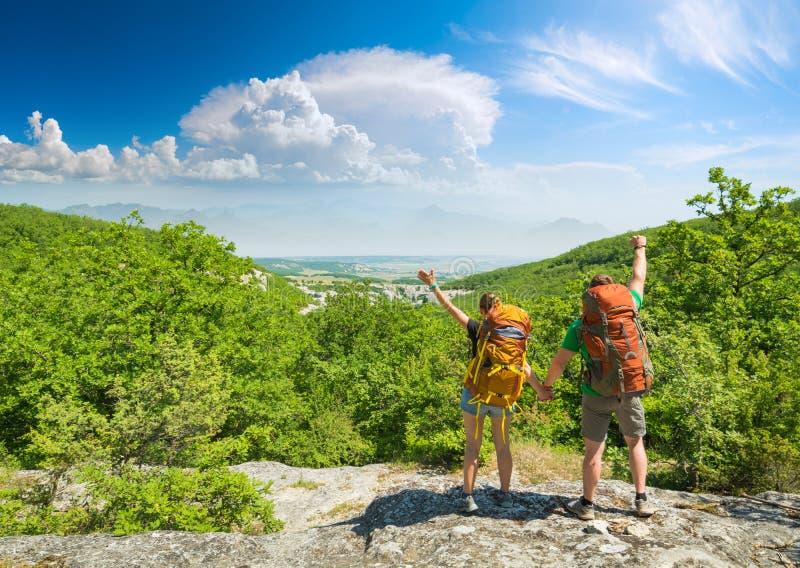 Caminhantes felizes com as trouxas no montanhas rochosas foto de stock royalty free