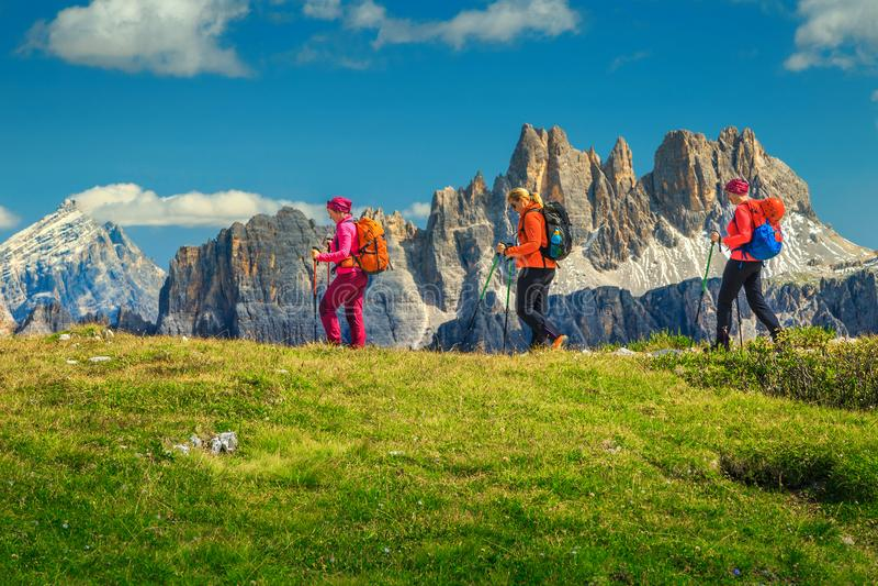 Caminhantes felizes da mulher com trouxas que andam nas montanhas, dolomites, Itália fotografia de stock