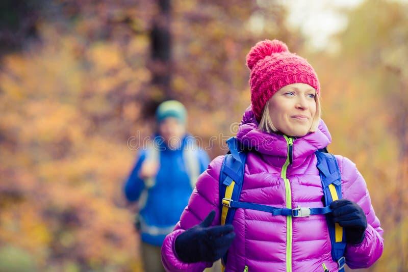 Caminhantes felizes dos pares que andam na floresta do outono fotos de stock royalty free