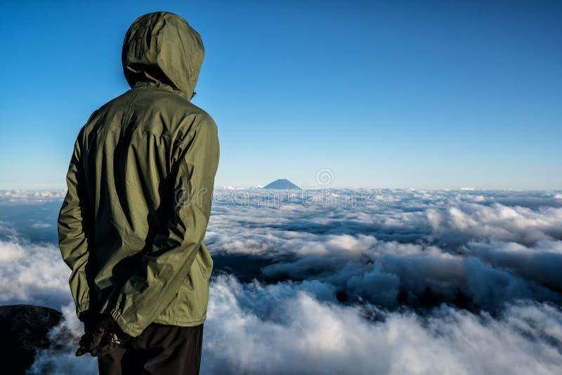 Caminhantes na cimeira do Mt Kita no por do sol, admirando o Mt Fuji na distância fotografia de stock royalty free
