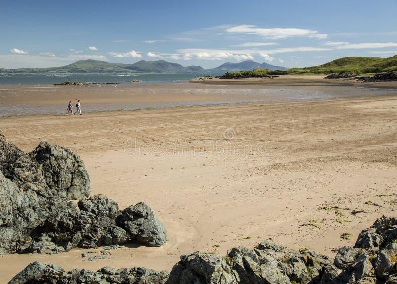 Caminhantes na praia em Newborough, Anglesey Gales imagem de stock