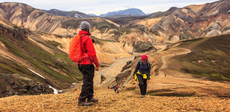 Caminhantes que escalam acima o monte em Landmannalaugar com cordilheiras multi-coloridas bonitas como um fundo imagens de stock