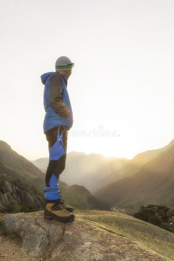 Caminhantes que olham a paisagem impressionante nas montanhas durante o nascer do sol foto de stock