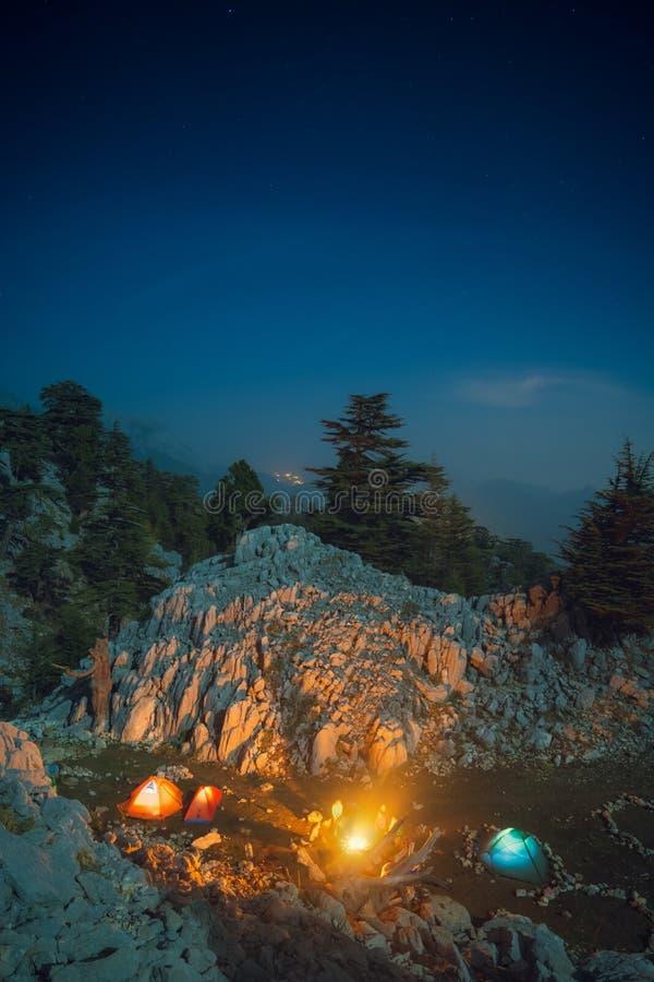 Caminhantes que sentam-se perto da fogueira sob o céu estrelado fotos de stock royalty free