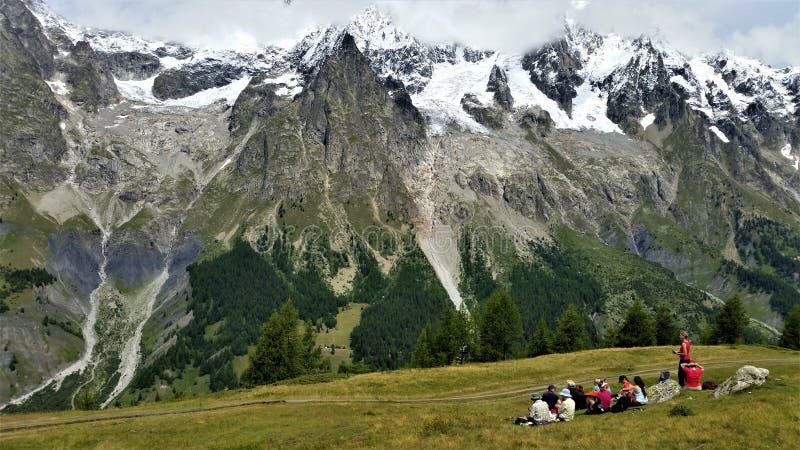 Caminhantes que tomam parte num piquenique abaixo dos cumes franceses neve-tampados foto de stock royalty free
