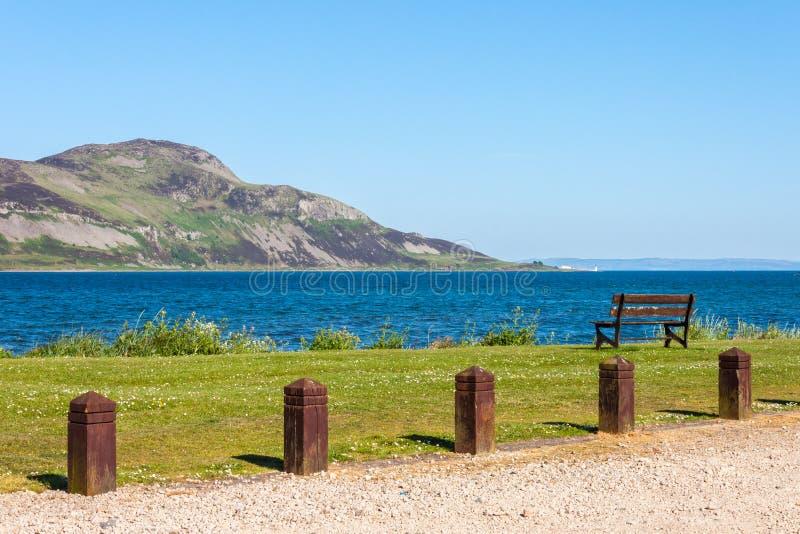 Caminho, banco, mar e ilha Ilha santamente, Lamlash, Arran, Scotl fotografia de stock