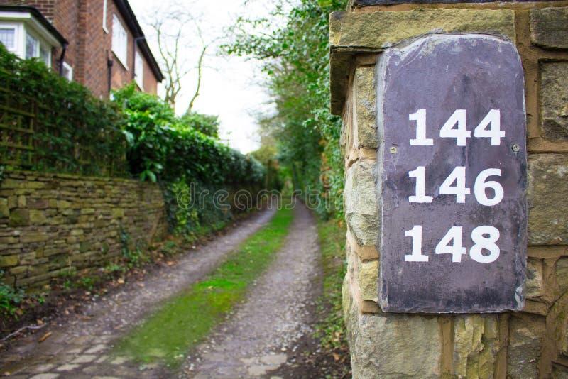 Caminho coberto de vegetação longo com números da ardósia em uma parede foto de stock royalty free