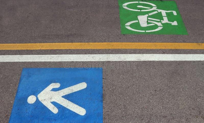 Caminho da cidade dividido em dois: o pedestre somente com o azul pintou a pista do sinal e do ciclismo com o símbolo verde pinta fotografia de stock royalty free