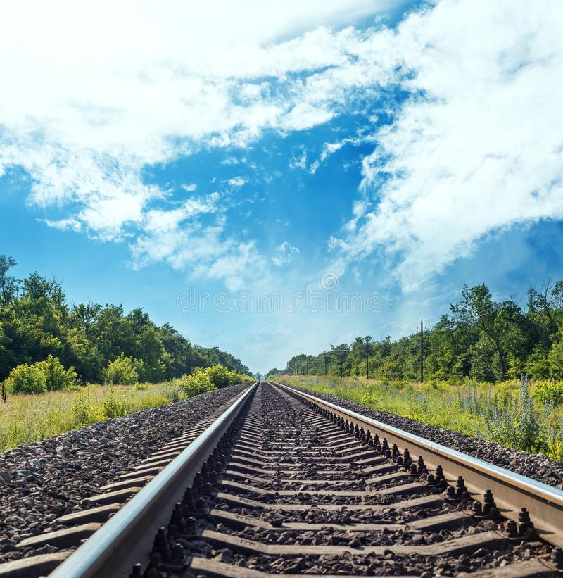 Caminho de ferro para o horizonte em prados verdes e céu azul com nuvens imagens de stock royalty free