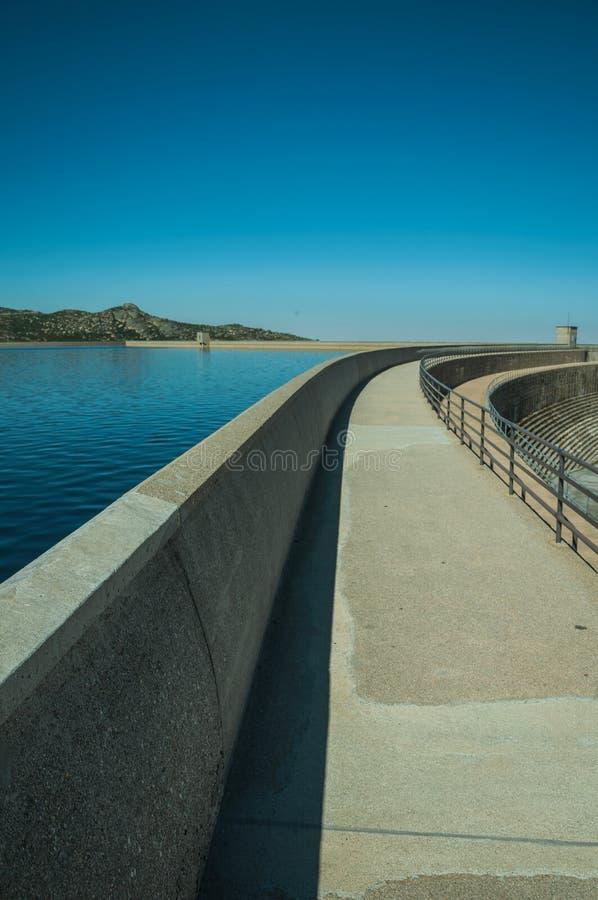 Caminho sobre a parede da represa que forma um lago em montanhas fotografia de stock