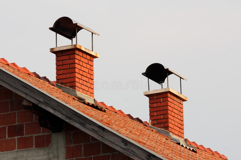 Camini del mattone rosso con protezione del metallo sulla cima sulla casa suburbana non finita della famiglia al tramonto immagine stock libera da diritti