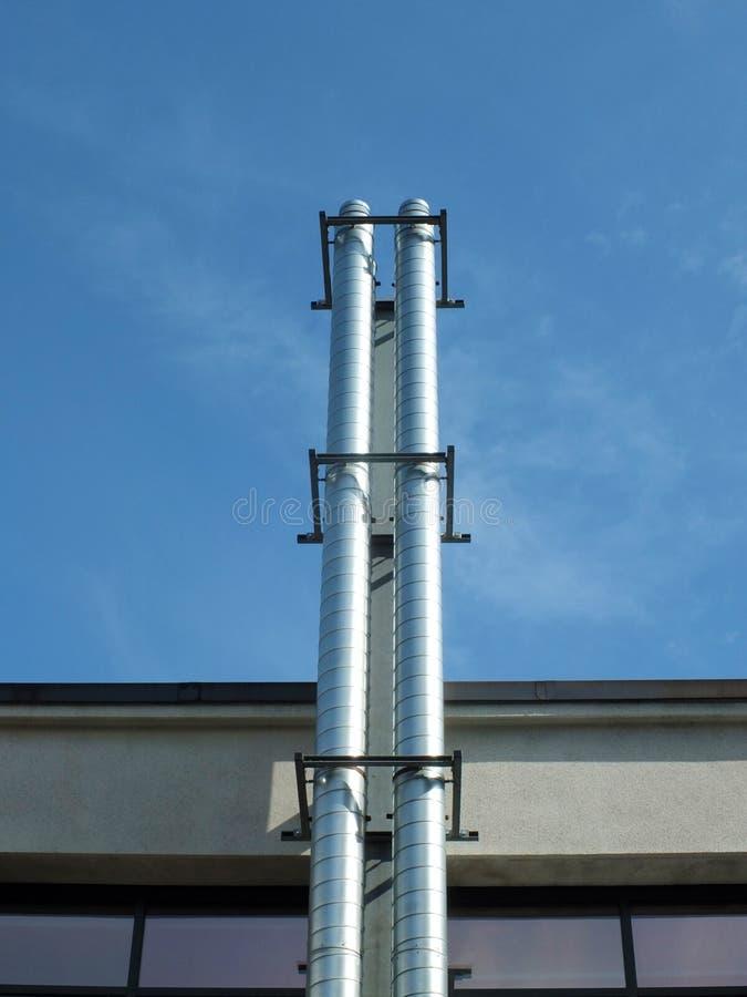 Camini industriali dell'estrazione del metallo d'acciaio brillante dal lato di una costruzione contro un cielo blu di estate con  fotografia stock libera da diritti