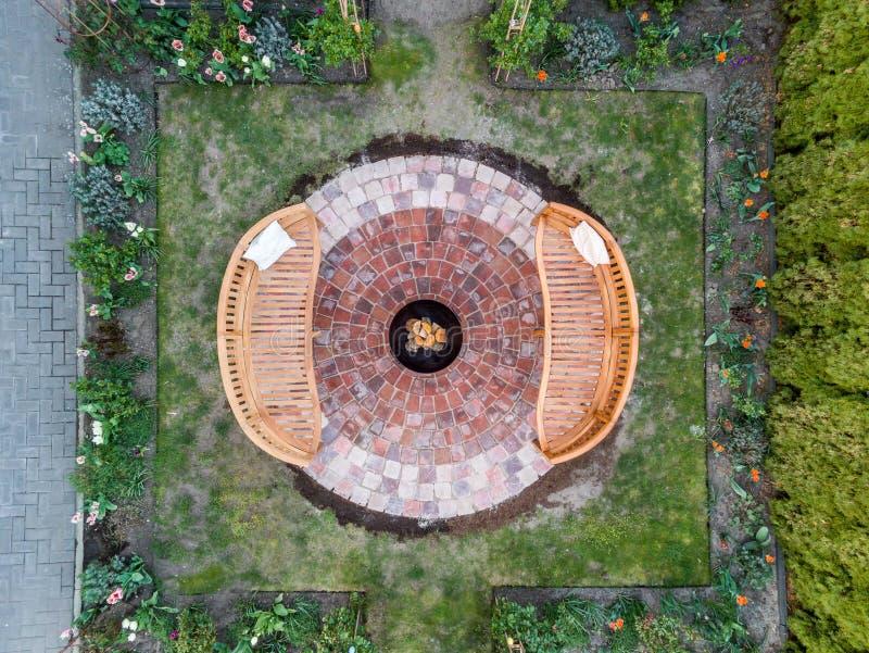 Camino accogliente nel giardino con due banchi e un braciere fotografia stock