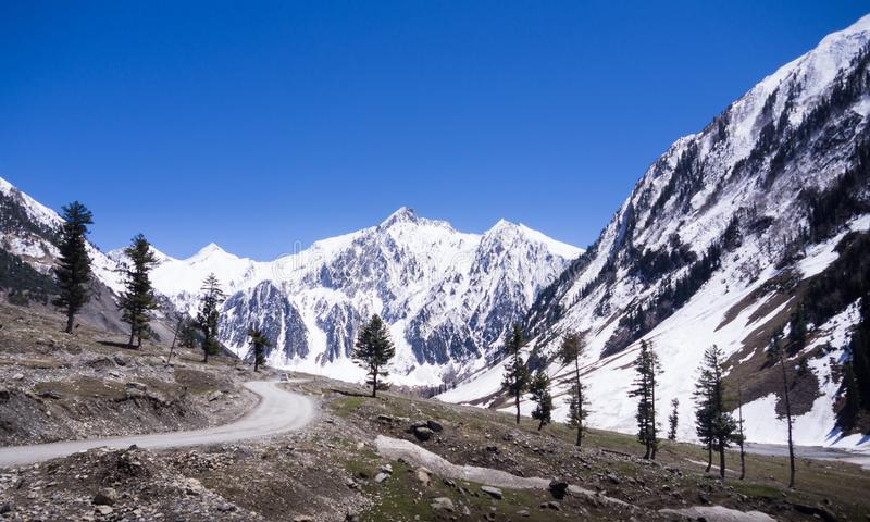 Camino alpino entre la montaña de la nieve fotografía de archivo libre de regalías
