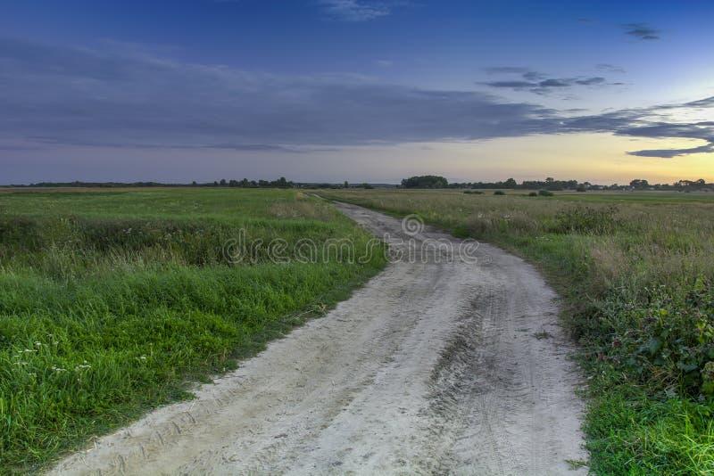 Camino arenoso rural a través de los campos, nubes después de la puesta del sol imágenes de archivo libres de regalías
