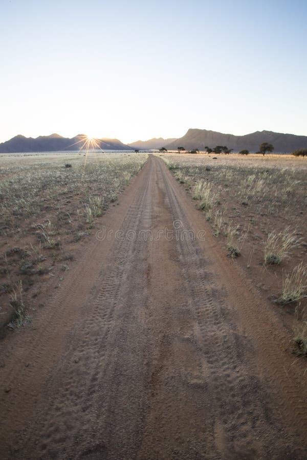 Camino bien usado, polvoriento del desierto a ninguna parte Namibia meridional Cerco del paisaje de la monta?a Sol de la estrella imagenes de archivo