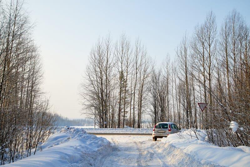 Camino blanco de la nieve con el coche entre árboles del invierno en bosque en un día soleado fotos de archivo libres de regalías