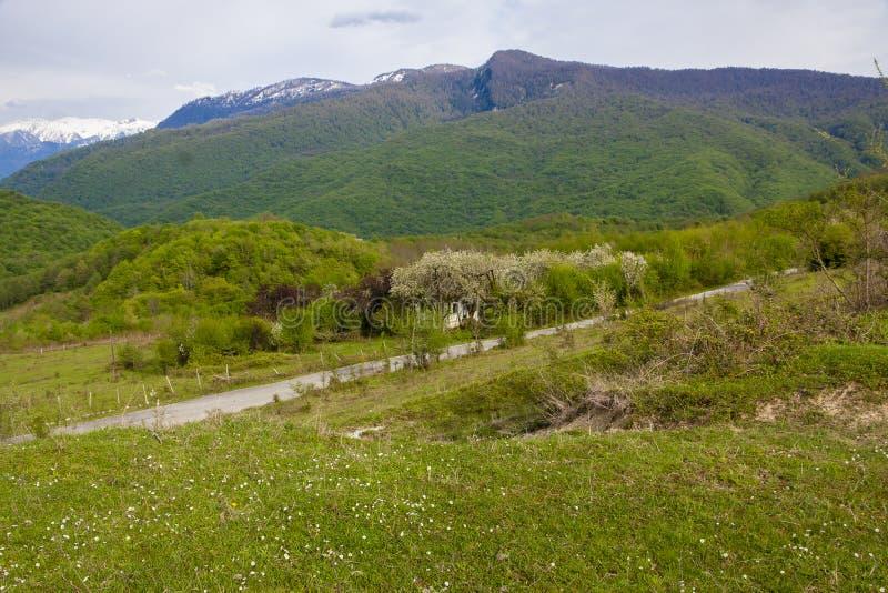 Camino cerca de la casa en montañas fotos de archivo