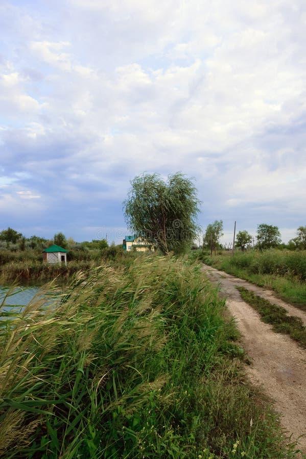 Camino cerca del río debajo del cielo nublado fotos de archivo libres de regalías