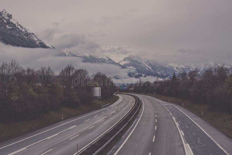 Camino con el árbol del borde de la carretera a las montañas en Interlaken foto de archivo libre de regalías