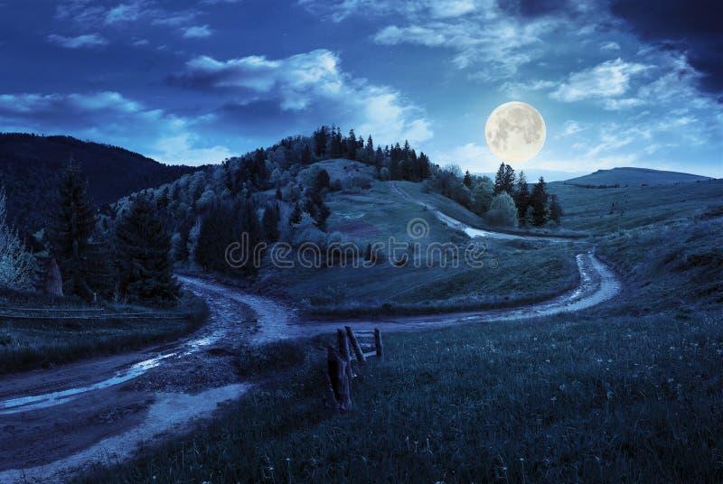 Camino cruzado en prado de la ladera en montaña en la noche imagenes de archivo