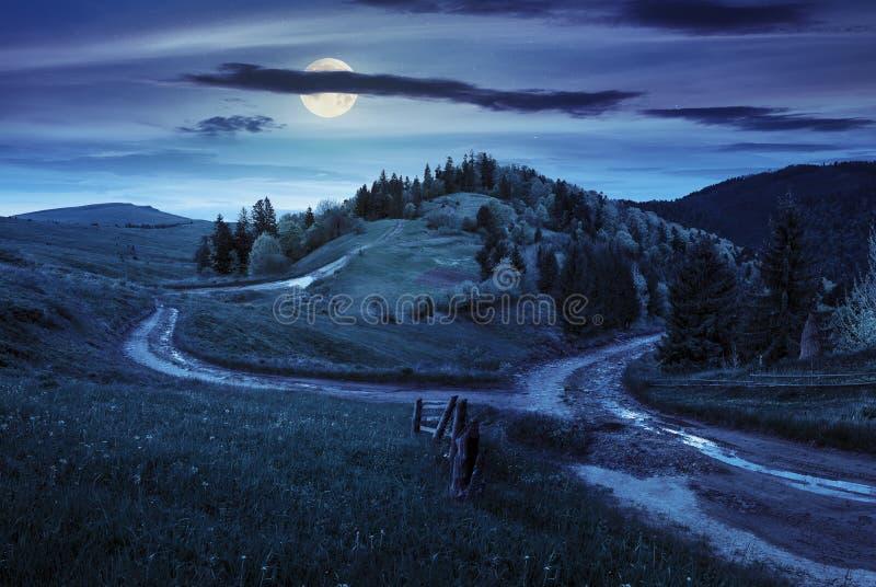 Camino cruzado en prado de la ladera en montaña en la noche foto de archivo