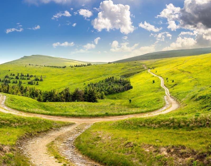 Camino cruzado en prado de la ladera en montaña en la salida del sol imagenes de archivo