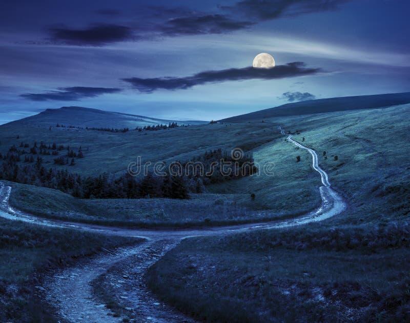 Camino cruzado en prado de la ladera en montaña en la salida del sol en la noche imagenes de archivo