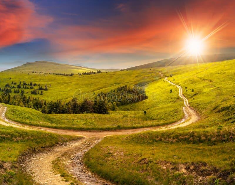 Camino cruzado en prado de la ladera en montaña en la salida del sol en la puesta del sol foto de archivo libre de regalías