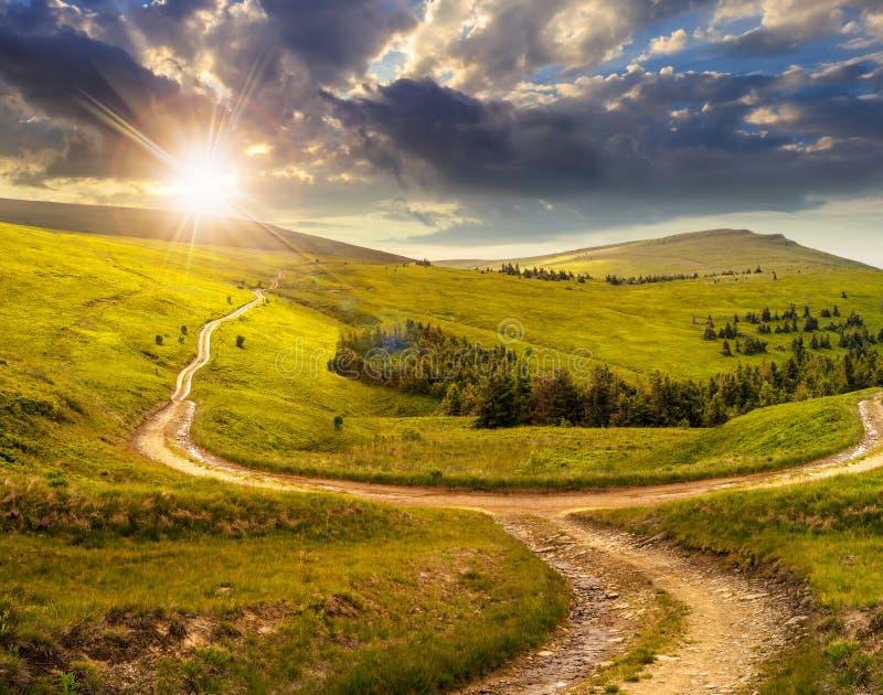 Camino cruzado en prado de la ladera en montaña en la salida del sol en la puesta del sol fotos de archivo