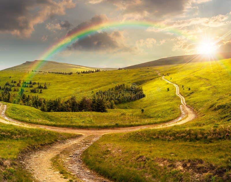 Camino cruzado en prado de la ladera en montaña en la salida del sol en la puesta del sol imagen de archivo