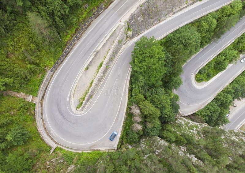 Camino curvado con los coches y el bosque hermoso imagenes de archivo