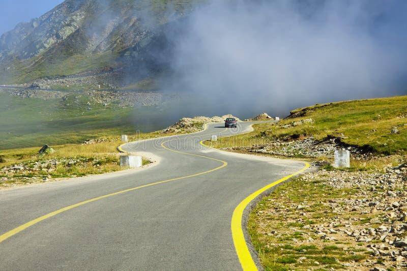Camino curvado en el paisaje de la montaña, Transalpina fotos de archivo