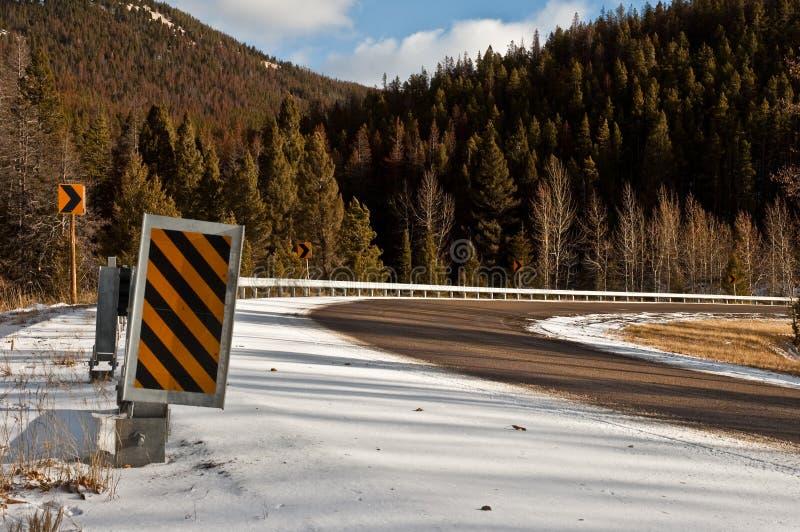 Camino Curvy del invierno con la muestra de la precaución fotos de archivo libres de regalías