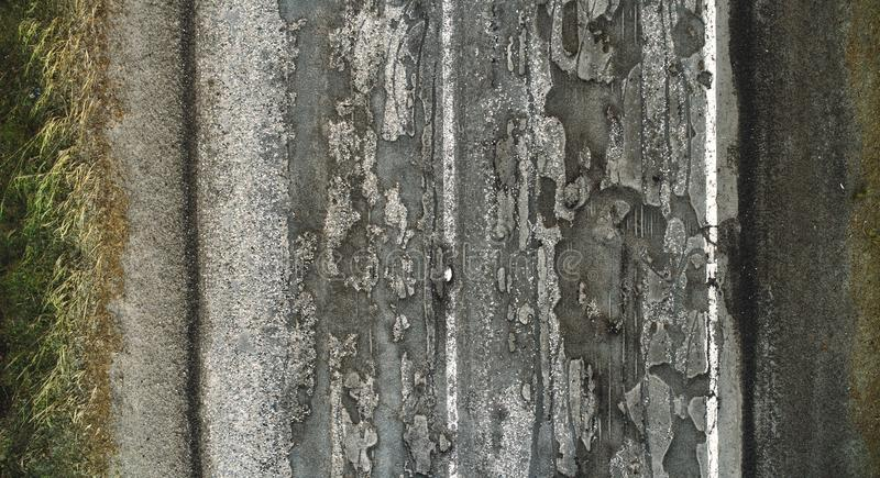 Camino dañado, blacktop agrietado del asfalto con los agujeros y remiendos fotos de archivo libres de regalías