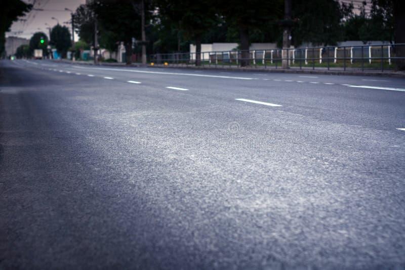 Camino de ciudad con nuevo asfalto A lo largo de él hay un callejón Los semáforos y los coches son visibles fotografía de archivo libre de regalías